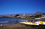 Tourists on the beach,Playa las Americas against the background of the mountains,tenerife, Canary Islands,Spain