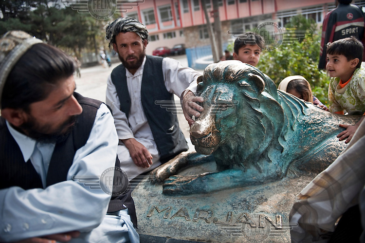 People surround a statue of Marjan the lion, who has become a legend at Kabul Zoo. He became blind after surviving a grenade attack carried out by the Mujahedin during the Soviet occupation of Afghanistan. After surviving many wars and conflicts he died of old age in 2002.