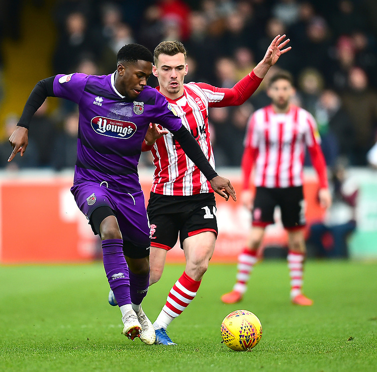 Grimsby Town's Mitch Rose shields the ball from  Lincoln City's Harry Toffolo<br /> <br /> Photographer Andrew Vaughan/CameraSport<br /> <br /> The EFL Sky Bet League Two - Lincoln City v Grimsby Town - Saturday 19 January 2019 - Sincil Bank - Lincoln<br /> <br /> World Copyright © 2019 CameraSport. All rights reserved. 43 Linden Ave. Countesthorpe. Leicester. England. LE8 5PG - Tel: +44 (0) 116 277 4147 - admin@camerasport.com - www.camerasport.com
