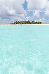 Blue Lagoon, Rangiroa Atoll, Tuamotu Archipelago, French Polynesia; the shallow, turquoise waters of the blue lagoon with a palm tree covered island in the distance