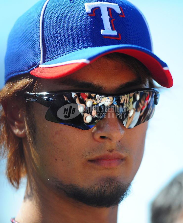 Mar. 1, 2012; Surprise, AZ, USA; Fans reflect in the sunglasses of Texas Rangers pitcher Yu Darvish as he signs autographs during spring training workouts at the practice fields at Surprise Stadium.  Mandatory Credit: Mark J. Rebilas-.