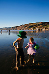 Ruthawna Collins, 4, of Forsyth, Missouri, plays along the shore of Pismo Beach, California with her brother Tobias, 10, on December 22, 2014. The trip was her first trip to the beach.