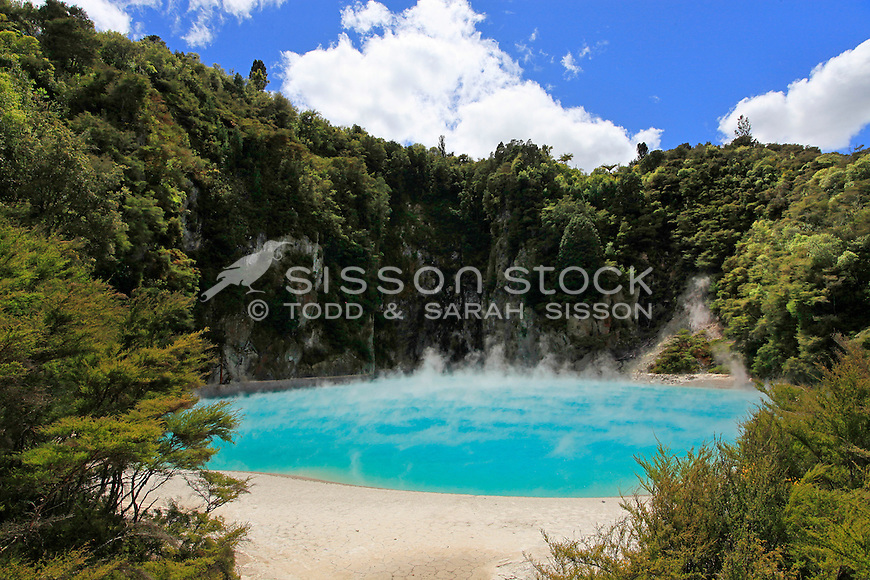 The steaming bright aqua waters of Inferno Crater at Waimangu Valley thermal scenic attraction near Rotorua, North Island, New Zealand