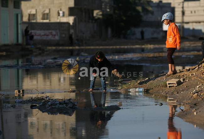 Palestinian children walk past a flooded street after heavy storms in Rafah refugee camp southern Gaza strip on 11 january 2013. In Gaza, cold weather and heavy rain flooded several of the tunnels running between the territory and Egypt as in the West Bank city of Ramallah, children and adults, including some policeman stopped their cruiser for an impromptu snowball fight. Photo by Eyad Al Baba