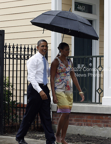 United States President Barack Obama holds his umbrella over himself and First Lady Michelle Obama as they tour the the Columbia Parc Apartment Development in New Orleans, Louisiana, Sunday, August 29, 2010. The Obamas visited New Orleans to mark the fifth anniversary of Hurricane Katrina.   .Credit: A.J. Sisco - Pool via CNP