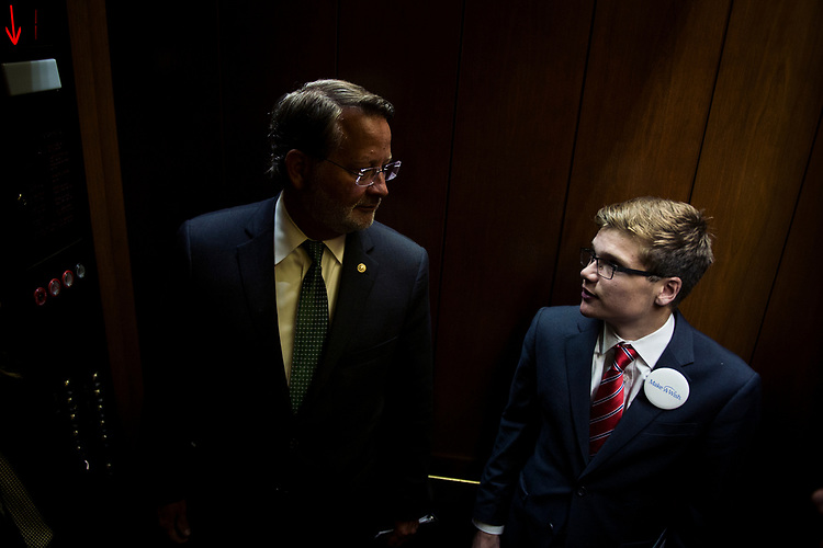 UNITED STATES: July 10: Make-A-Wish recipient and 'U.S. Senator For a Day' Thomas Stephenson and Sen. Gary Peters', D-Mich., ride the elevator to the Senate Subway in the Hart Senate Office Building Tuesday July 10, 2018. (Photo by Sarah Silbiger/CQ Roll Call)