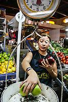 Maria Sandoval  pesa algunas manzanas para empacar y posteriormente poner a la venta en el mercado municipal
