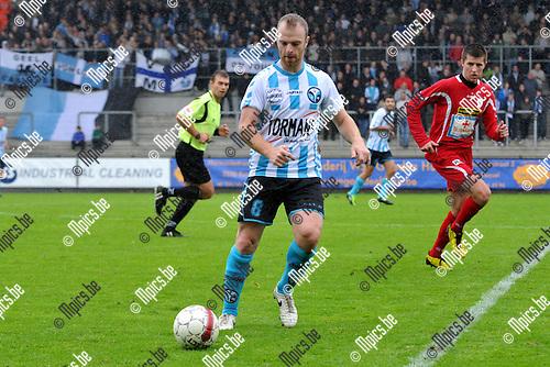 2011-10-09 / voetbal / seizoen 2011-2012 / Verbroedering Geel-Meerhout - Turnhout / David Vandecauter (l) (VGM) aan de bal.  Op de achtergrond kijkt Mantas Kuklys (r) (Turnhout) toe.