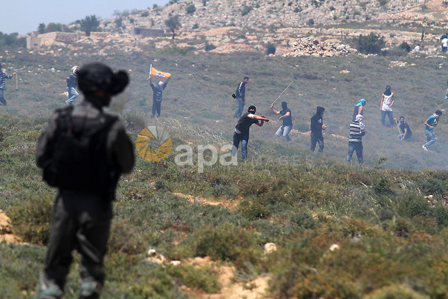 Palestinian demonstrators from the West Bank village of Deir Jarir, northeast of Ramallah, throw stones at Israeli soldiers during clashes following a march against construction on their land by members of the nearby Jewish settlement of Ofra on April 26, 2013. Photo by Issam Rimawi