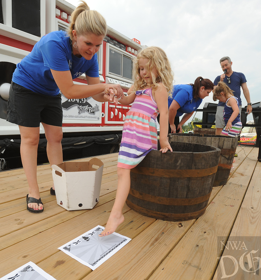 NWA Democrat-Gazette/ANDY SHUPE<br /> Participants stomp grapes Tuesday, Aug. 4, 2015, during the 117th annual Tontitown Grape Festival. The festival continues through Saturday. Visit nwadg.com/photos to see more photographs from the festival.