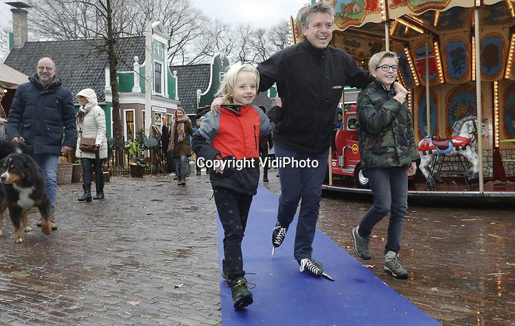Foto: VidiPhoto<br /> <br /> ARNHEM – Met een 300 meter lange kluunwedstrijd, die gewonnen werd door de bekende schaatser en oud-deelnemer aan de Elfstedentocht Erik Hulzenbosch, is zaterdag het winterseizoen in het Nederlands Openluchtmuseum in Arnhem geopend. Samen met de nummers 2 en 3 werd hij gehuldigd. Dat gebeurde tijdens herfstachtige omstandigheden met veel wind en regen. Het museumpark is desondanks ingericht alsof het volop winter is met ijs(glij)baan, koek en zopie, midwinterhoornblazers, winterse ambachten en vuurkorven. Sommige kluners kregen wat hulp van familie of kwamen hijgend en puffend over de streep. De winteropenstelling van het Openluchtmuseum duurt tot en met 20 januari 2019.