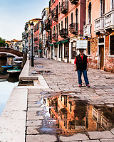 A Venetian Baker using his head to take his fresh Italian rolls to market in Venice Italy. <br />