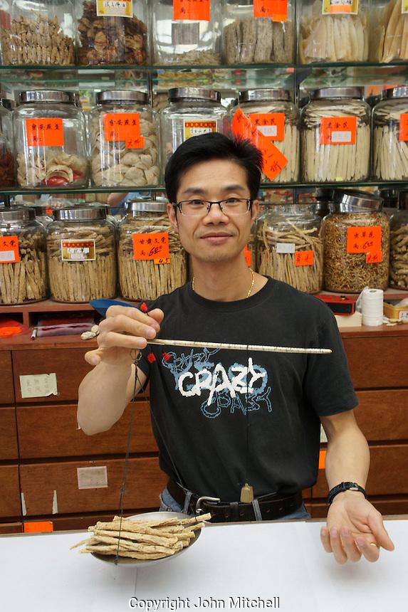Chinese herbalist using a handheld balance scale, Chinatown, Vancouver, British Columbia, Canada