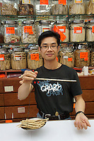 Chinese herbalist using a handheld balance scale, Chinatown, Vancouver, British Columbia, Canada