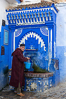 Chefchaouen, Morocco.  Man Filling Water Bucket at Public Water Tap.