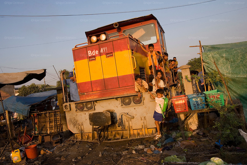 ROYAL CAMBODIAN RAILWAYS. The journey from Phnom Penh to Battambang is the last working route. A passenger train, operates only at weekends. A Czech made diesel locomotive, leaves the capital Saturday morning, arriving in Battambang 22 hours later in the dead of night, and returns on Sunday. Max speed is about 30kmh, often slower due to the track's terrible condition. Carriages are dilapidated, with holes in the floor and only spaces for windows. Passengers sit or sleep on hardwood bench seats, hammocks, or on the floor of cargo carriages. The drivers, controllers & guards add to their small monthly pay by charging for local passengers and cargo; from motor bikes and local produce to timber loaded aboard at the 30 stations along the route. This together with other trains and farm vehicles further slows the journey. In rural areas, the track is a lifeline, and used for local transport on 'bamboo trains' powered by belt-motors, or pushcarts. Boom towns, with a 'goldrush mentality' near the rapidly depleted rainforest, are a hive of activity, with logging as their resource, where children workers even gamble away their earnings on cardgames. In the city, the railway has a life of its own, where people live and work nearby or on the track itself. Market stalls, restaurants, chairs and tables, are removed only briefly, when the infrequent train passes!///The train passes between market stalls in Phnom Penh