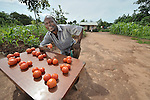 A man sells tomatoes in front of his home in Dundube Kadambo, northern Malawi.