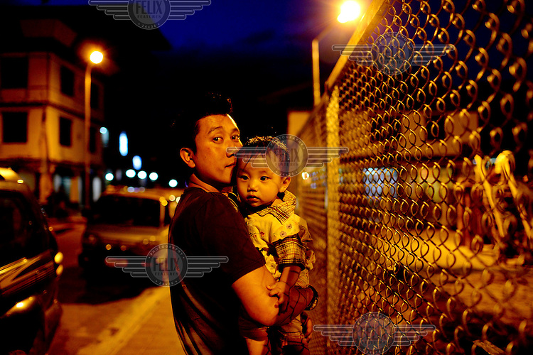A father holds his child on a street at night in Paro.