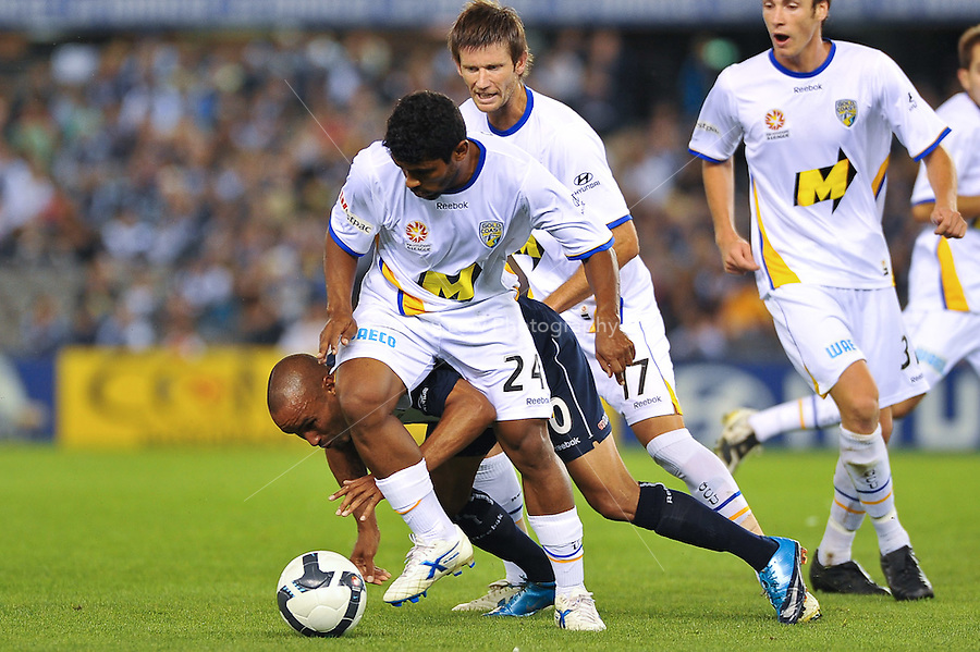 MELBOURNE, AUSTRALIA - NOVEMBER 28, 2009: Archie Thompson from Melbourne Victory is tackled by Zac Anderson in round 16 of the A-league match between Melbourne Victory and Gold Coast United at Etihad Stadium on November 28, 2009 in Melbourne, Australia. Photo Sydney Low www.syd-low.com