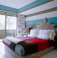 The colourful throws, pillows and headboard in the master bedroom are all designed by Muriel Brandolini