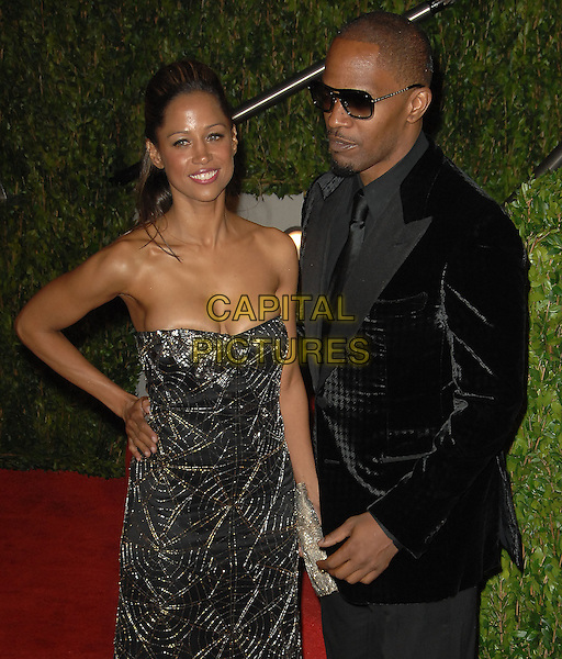 STACEY DASH & JAIME FOXX.The 2010 Vanity Fair Oscar Party held at The Sunset Tower Hotel in West Hollywood, California, USA..March 7th, 2010.oscars half length black suit strapless beds beaded dress hand on hip gold silver jamie couple sunglasses shades .CAP/RKE/DVS.©DVS/RockinExposures/Capital Pictures.