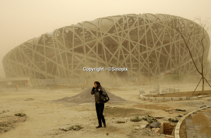 A young lady covers her face with a hand amid a sandstorm  in the construction site of National Stadium for Beijing 2008 Olympic Games in Beijing, China. 18-Mar-2008