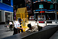 "NEW YORK, NEW YORK - SEPTEMBER 3: A security worker wakes up a homeless at Times Square on September 3, 2020 in New York.  U.S. President Trump has ordered to the federal government to begin the process to defund NYC and three other cities where protest ""lawless"" were allowed and police budgets were cut, rising violent crime. (Photo by Eduardo MunozAlvarez/VIEWpress via GettyImages)"