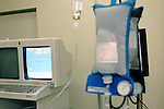 A dual monitor can be seen at the left hand side of the picture. One monitor is linked to a computerized system with software for image collection. The other screen will probably be used to view the live angiography procedure. Bags of fluids can be seen on the right-hand side of the picture. Royalty Free