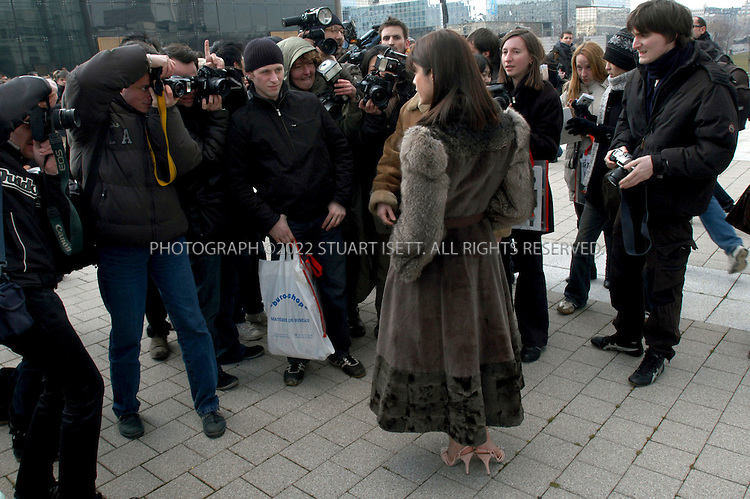 3/6/2005--Paris, France..Photographers shoot a visitor arriving for the Louis Vuitton show at the Paris Fashion Week. Despite near freezing temperatures hundreds turned out at the Serre du Parc Andre Citroen to see the Louis Vuitton collection...All photographs ©2003 Stuart Isett.All rights reserved.