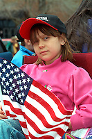 Inquisitive girl age 10 holding American flag at Cinco de Mayo.  St Paul Minnesota USA