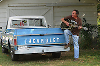 NWA Democrat-Gazette/FLIP PUTTHOFF <br /> BREAK-TIME SONG<br /> Matt James of Rogers sings and plays during a break from his job doing maintenance Tuesdsay Sept. 22 2015 on a home near Third and Locust streets in Rogers. James writes his own tunes and sang an original song while leaning on his 1971 Chevrolet pickup.