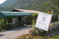 A road side bar and a sign half falling down saying that USAid is giving financial aid to this region. Near Dupilo, Golubovic Montenegro, Balkan, Europe.