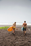 USA, Hawaii, The Big Island, paddle boarders walk towards the surf in Waipio Valley