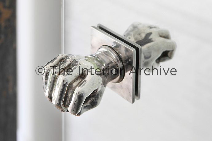 A  metal doorknob in the form of a hand is reflected in the glass door of the kitchen