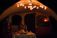 Switzerland. Canton Ticino. Tenero. Camping Campofelice. Electric lights at nighttime. Jan Scheppink and his wife, both from Holland, sit in front of their caravan and talk together in the evening hours. A caravan, travel trailer, camper or camper trailer is towed behind a road vehicle to provide a place to sleep which is more comfortable and protected than a tent. It provides the means for people to have their own home on a journey or a vacation. Campers are restricted to designated sites for which fees are payable. 21.07.2018 © 2018 Didier Ruef