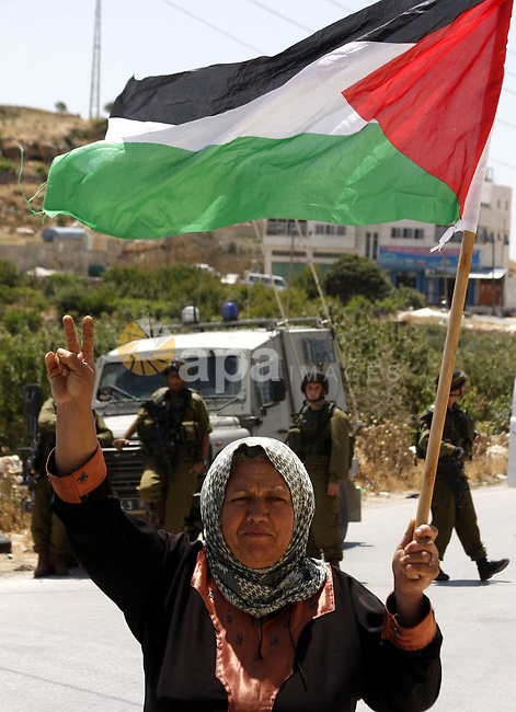 A Palestinian woman waves her national flag as she walks near Israeli soldiers during a demonstration against Israel's separation barrier in the West Bank village of Maasarah, near the biblical town of Bethlehem, on May 28, 2010. Photo by Mamoun Wazwaz