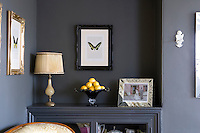 To create a feeling of space in the living room a built-in cupboard has been painted the same shade of dark graphite as the walls