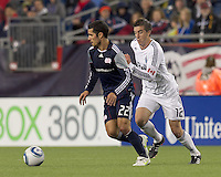 New England Revolution forward Benny Feilhaber (22) dribbles as Vancouver Whitecaps FC midfielder Jeb Brovsky (12) pressures. In a Major League Soccer (MLS) match, the New England Revolution defeated the Vancouver Whitecaps FC, 1-0, at Gillette Stadium on May14, 2011.