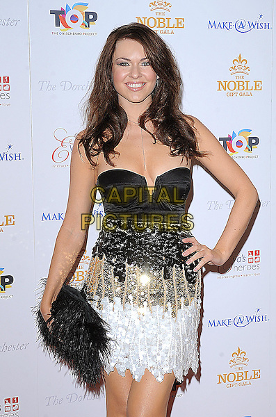 ZOE SALMON.Attending The Noble Gift Gala, Dorchester Hotel, London..13th March 2010 .half length black dress hand on hip gold white strapless sequins sequined clutch bag skirt corset top feathers .CAP/BEL.©Tom Belcher/Capital Pictures.