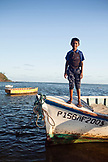 MAURITIUS, the son of a fisherman stands on the front of a boat after a day of fishing, Bel Ombre, Indian Ocean