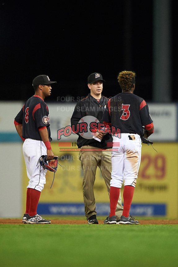 Batavia Muckdogs shortstop Anfernee Seymour (3) is looked at by trainer Eric Reigelsberger as second baseman Giovanny Alfonzo (8) looks on during a game against the Williamsport Crosscutters on August 27, 2015 at Dwyer Stadium in Batavia, New York.  Batavia defeated Williamsport 3-2.  (Mike Janes/Four Seam Images)