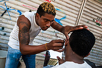 A young Colombian man shaves a friend's beard with a razor blade in the market of Bazurto, Cartagena, Colombia, 15 April 2018.