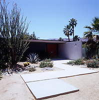 A concrete path weaves its way through the sandy terrain at the entrance to the low-lying property