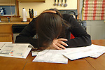 young adult woman sitting at kitchen table stressed by pile of unpaid bills.