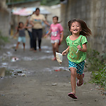 A girl runs through the streets in Pulilan, a village in Bulacan, Philippines, where the Kapatiran-Kaunlaran Foundation (KKFI) sponsors a preschool. <br /> <br /> KKFI is supported by United Methodist Women.