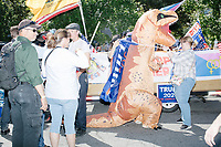 A man wears an inflatable dinosaur suit and a Trump 2020 flag in the Straight Pride Parade in Boston, Massachusetts, on Sat., August 31, 2019. The parade was organized in reaction to LGBTQ Pride month activities by an organization called Super Happy Fun America.