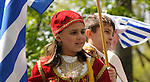 Greek Parade in New York City. Kids in traditional clothing and holding flags, ride on a float in the Greek Parade in New York City.