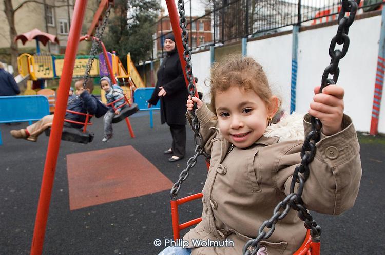 Children play on swings at Lisson Street Gardens in Paddington, London