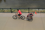 Father on bike pulling baby carriage on a sidewalk, Denver, Colorado. .  John offers private photo tours in Denver, Boulder and throughout Colorado. Year-round.