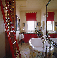 Stone has been used to clad the bath as a balance to the shiny porcelain and a red ladder is used as a towel rail